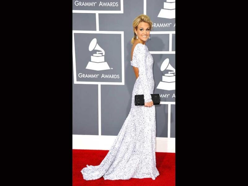 Carrie Underwood looks average in a shimmering white-silver Gomez-Garcia gown with a Swarovski black clutch.