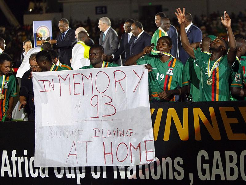 Zambia's players hold a banner in memory of the 1993 plane crash that killed the Zambia team in Gabon, as they celebrate their victory of the African Cup of Nations after their final soccer match against Ivory Coast at Stade de l'Amitie in Libreville, Gabon. (AP Photo/Francois Mori)