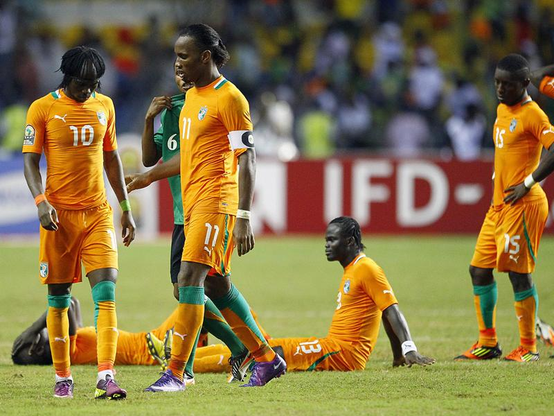 Ivory Coast's Gervinho, left, and captain Didier Drogba, second left, react with teammates after they lost on penalty kicks against Zambia during their African Cup of Nations final soccer match at Stade de L'Amitie in Libreville, Gabon. (AP Photo/Francois Mori)