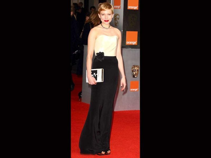 Michelle Williams kept it simple as she is dressed in a dual colour outfit. The book clutch, however, was an interesting accessory.