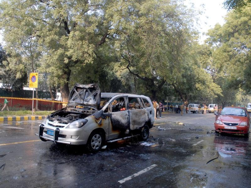 Forensic expert examining an Israel embassy car which caught fire after a blast in New Delhi.
