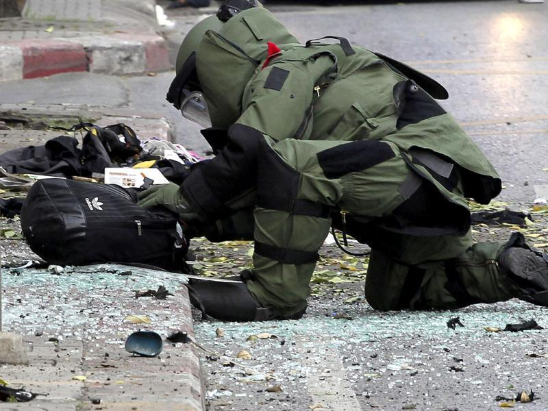 A Thai Explosive Ordnance Disposal (EOD) official makes a check on a backpack that was left on the bomb site by a suspected bomber in Bangkok. (AP Photo/Apichart Weerawong)