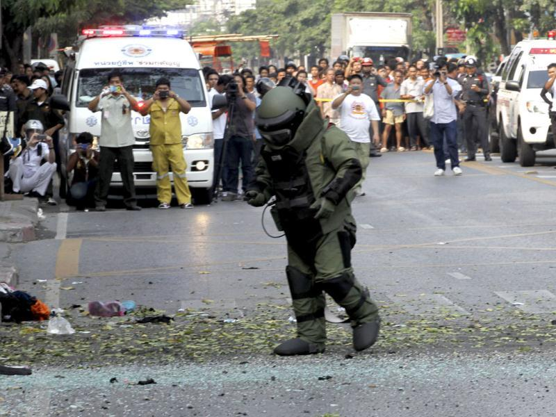 A Thai Explosive Ordnance Disposal (EOD) official examines the bomb site in Bangkok, Thailand. (AP Photo/Apichart Weerawong)
