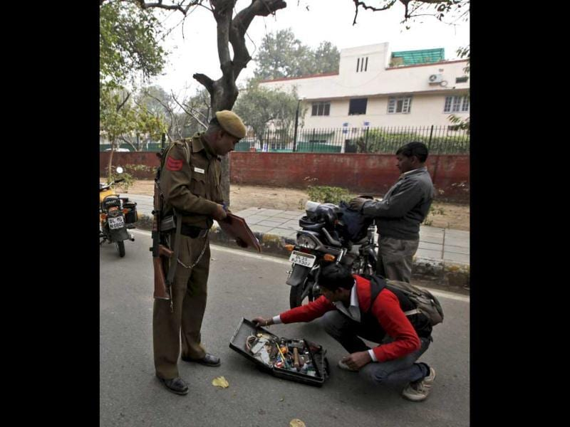 A policeman checks the contents of a bag carried by a motorcycle rider at a check point near the Israeli embassy in New Delhi. An Israeli embassy car blew up February 13 in the country's capital, injuring an Israeli diplomat and one other person, but it was not immediately known whether the explosion was caused by a bomb, officials said. Israel assailed Iran as the world's
