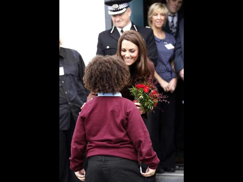 Britain's Catherine, Duchess of Cambridge, receives Valentine's Day gifts from 8 year old Jaqson Johnston-Lynch during a visit to The Brink, an alcohol-free bar in Liverpool, northern England. Reuters/Darren Staples