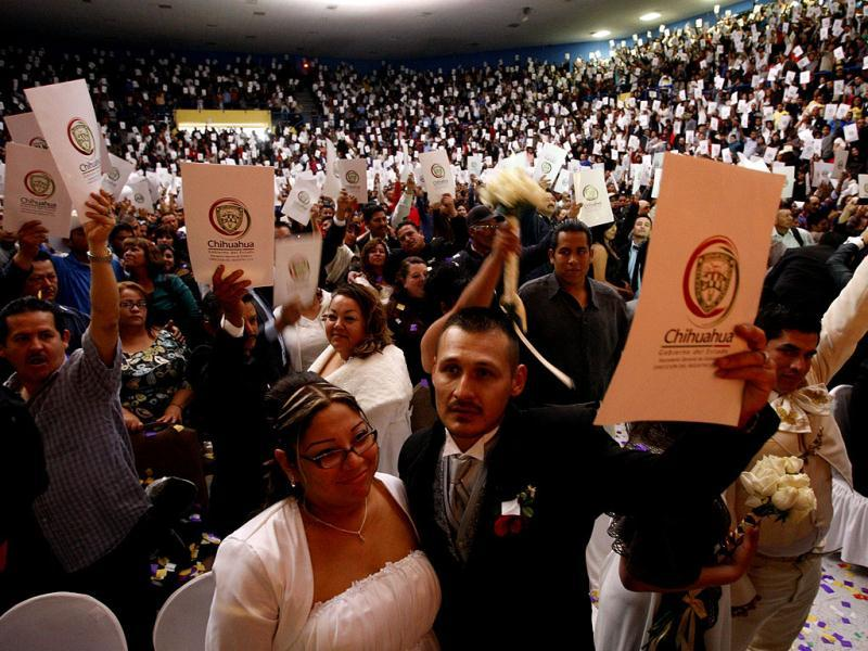 Newly married couples hold up their marriage license after a mass wedding in Ciudad Juarez. The mass wedding ceremony was held for 3,121 couples on Valentine's day. Reuters/Jose Luis Gonzalez