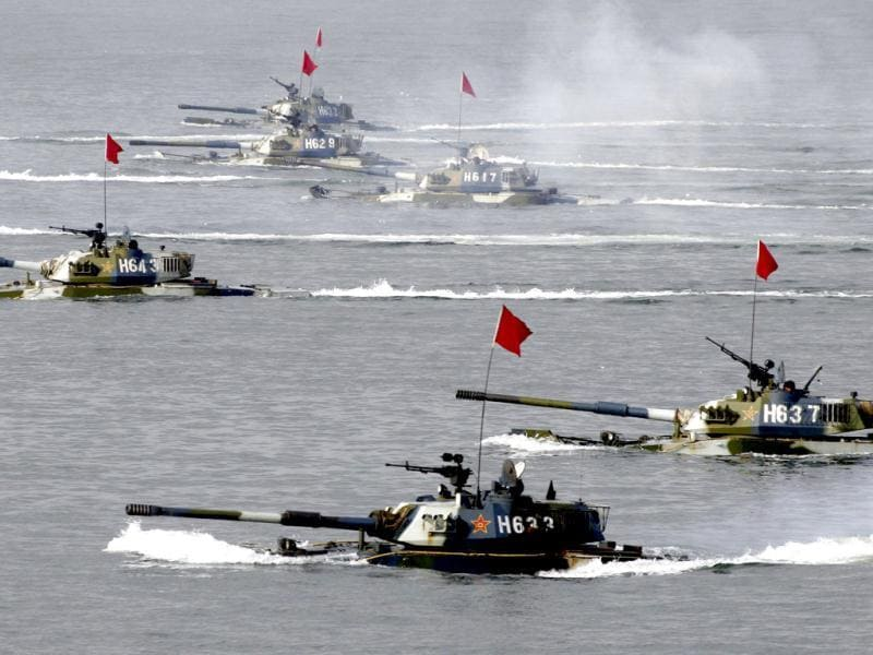 Amphibious tanks taking part in the Sino-Russia joint military exercise are seen in waters near eastern China's Shandong peninsula in this file photo. As looming budget cuts force the Pentagon to plan for a smaller US navy, China is accelerating the launch of new, increasingly capable warships as part of a sustained drive to become a major maritime power. Reuters/China Newsphoto/Files