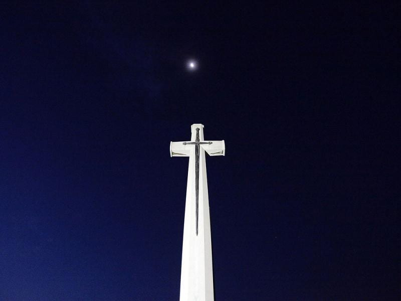 The moon is seen above a cross at the Kranji Commonwealth War Memorial Cemetery before an Australian memorial service in Singapore. The dawn service was held to commemorate the 70th anniversary of the fall of Singapore during World War II. Reuters/Tim Chong