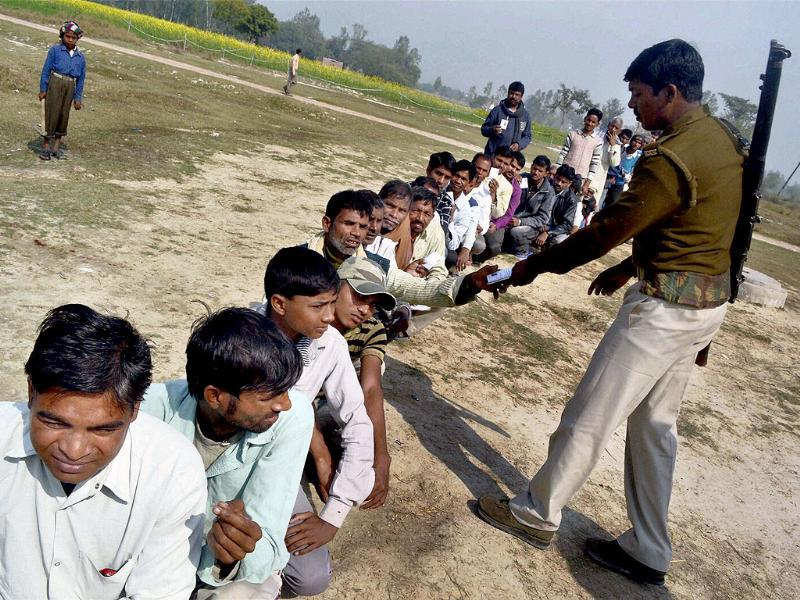 A security person checks the identity cards of the voters as they wait to cast their votes at a polling station, during the 3rd phase of UP assembly polls in Jaunpur. (PTI Photo)