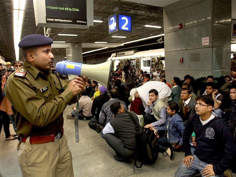 A security person makes an announcement as passengers take positions at the Khan Market Metro Station during a coordinated mock drill organised by Delhi Disaster Management Authority on earthquake-preparedness in New Delhi. PTI Photo/Subhav Shukla