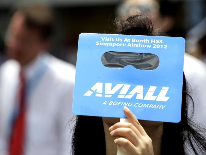 A woman looks at an aerial display through a cardboard visor during the Singapore Airshow in Singapore. (Reuters)