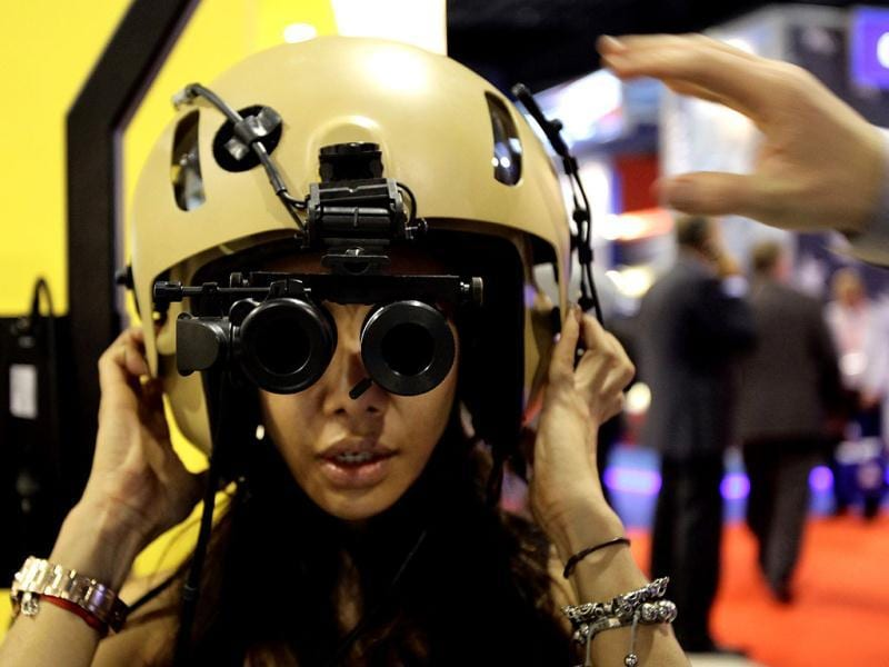 A visitor tries on an Aviation Night Vision Imaging System/Heads Up Display at the Elbit Systems booth at the Singapore Airshow in Singapore.(Reuters)