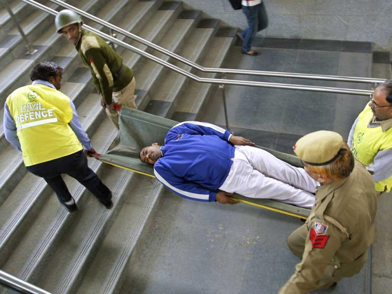Policemen and disaster management officials perform a mock rescue operation during a disaster drill checking the alertness and preparedness of various agencies in the event of a major earthquake, at a metro station, in New Delhi. AP Photo/Saurabh Das