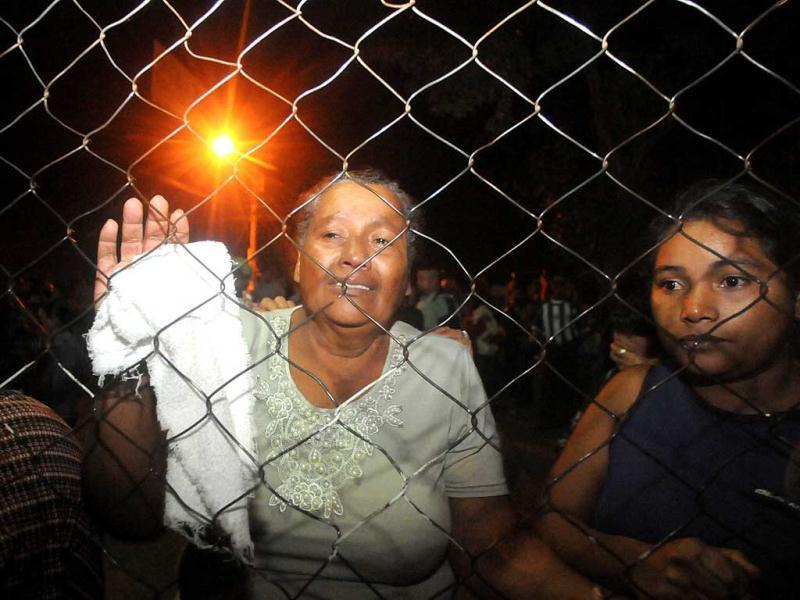 Inmates' relatives stand at the gates of the prison in Comayagua, Honduras. AP
