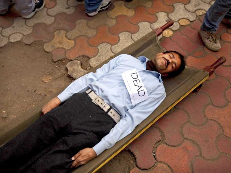 A man pretends to be dead as he lays on a stretcher during a disaster drill to check the preparedness of various agencies in the event of a major earthquake, in New Delhi. AP Photo/Kevin Frayer