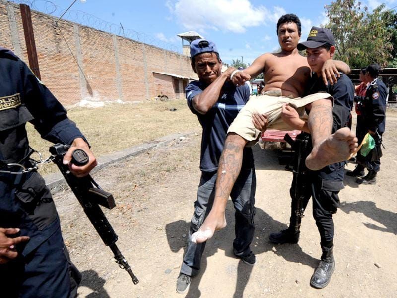 Police personnel carry an injured inmate out of the National Prison compound in Comayagua, (Honduras.topshots/AFP photo)