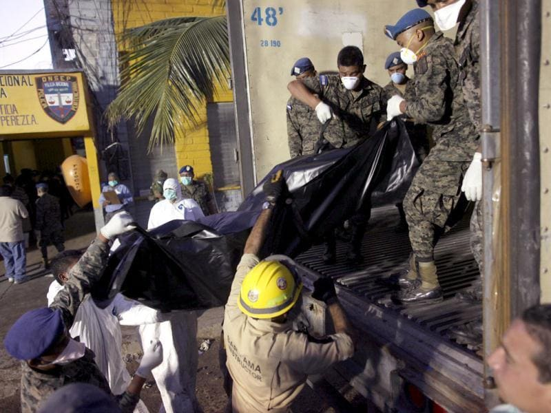 Soldiers and forensic workers load into a truck bodies of inmates killed during a fire inside the prison in Comayagua, Honduras. (AP Photo/Esteban Felix)