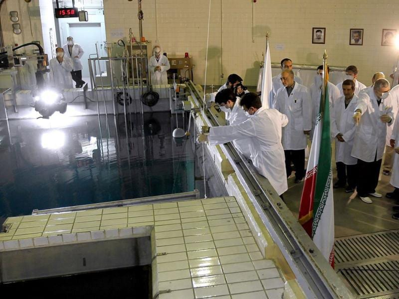 In this photo released by the Iranian President's Office, Iranian President Mahmoud Ahmadinejad, right is escorted by technicians during a tour of Tehran's research reactor centre in northern Tehran, Iran. (AP Photo/Iranian President's Office)