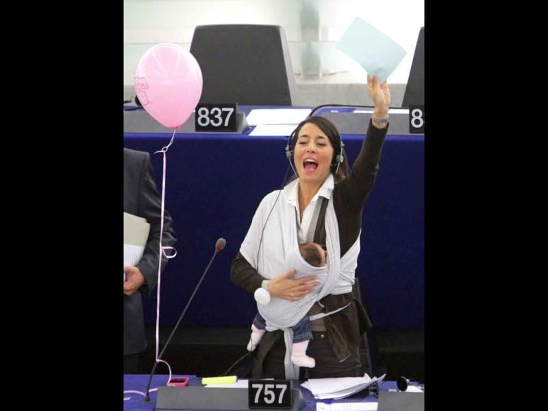 Ronzulli raises her hand to speak as she takes part with her baby in a voting session on the working conditions of women at the European Parliament in Strasbourg, October 20, 2010. Reuters/Jean-Marc Loos