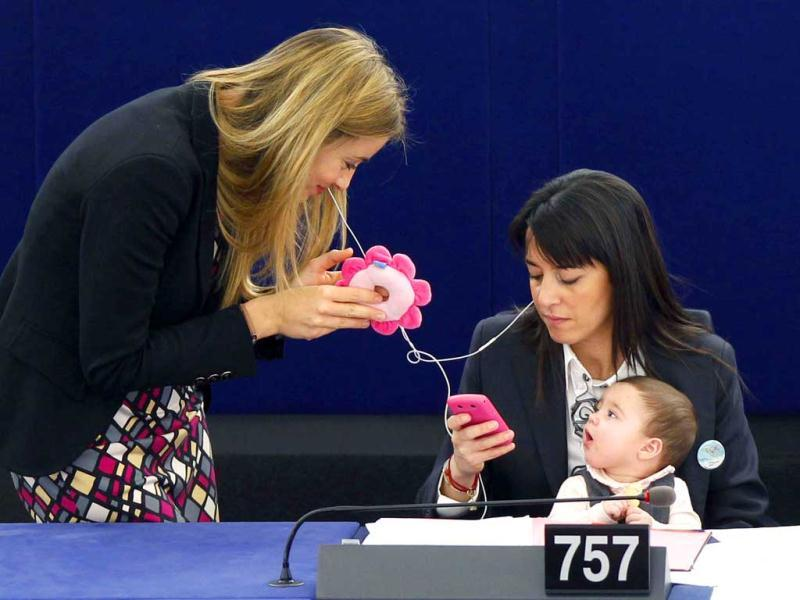 Ronzulli holds her baby as she talks with fellow MEP Barbara Matera during a voting session at the European Parliament in Strasbourg to mark the International Women's Day, March 8, 2011. Reuters/Vincent Kessler