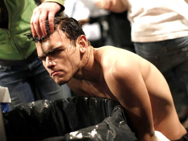 A model has dye rinsed out of his hair over a garbage bin backstage before the Custo Barcelona show Fall/Winter 2012 collection show during New York Fashion Week.