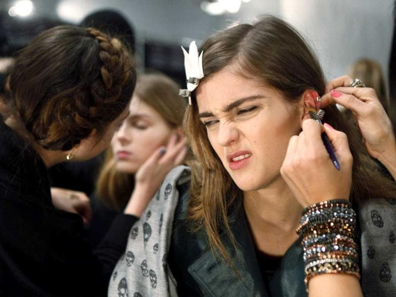 A model winces as she has an earring placed backstage before the Rebecca Taylor Fall/Winter 2012 show during New York Fashion Week. Reuters