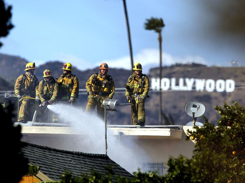 Firefighters battle a blaze at a house where authorities say at least three people were shot and wounded in east Los Angeles. AP/Patrick T. Fallon