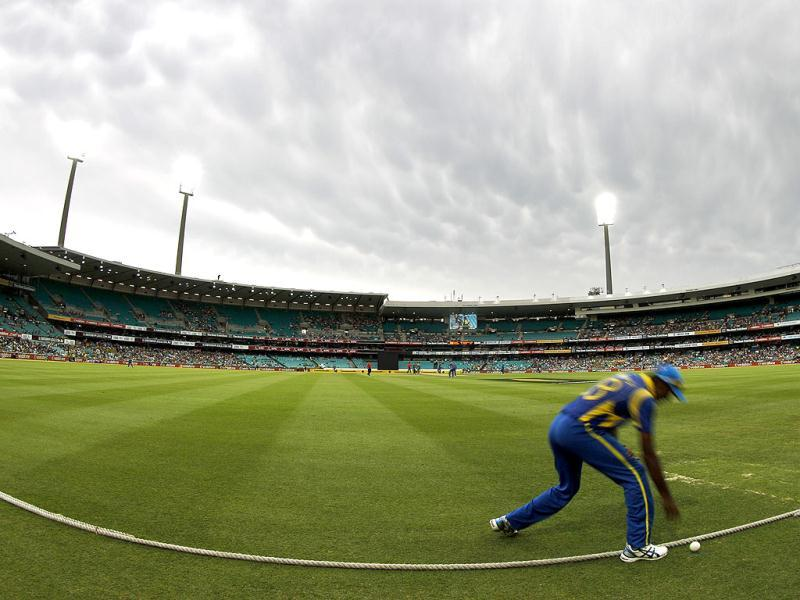 Sri Lanka's Farveez Maharoof picks up the ball from the boundary as storm clouds move over the Sydney Cricket Ground during their one-day international cricket match against Australia in Sydney. (Reuters/Tim Wimborne)