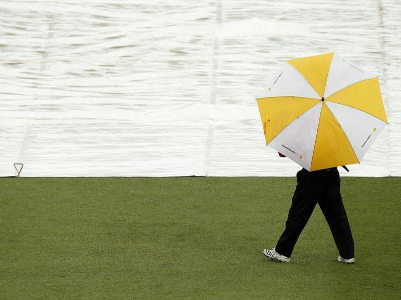 An umpire walks past the covered wicket when rain delayed play in the one-day international cricket match between Australia and Sri Lanka in Sydney. (Reuters/Tim Wimborne)