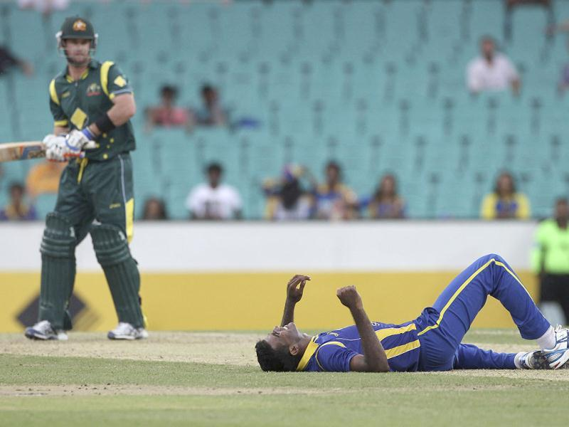 Sri Lanka cricket player Farveez Maharoof (R) lies on the pitch after missing a catch hit by Australia's Daniel Christian during a ODI cricket match against Australia at the Sydney Cricket Ground in Sydney, Australia. (AP Photo/Rob Griffith)