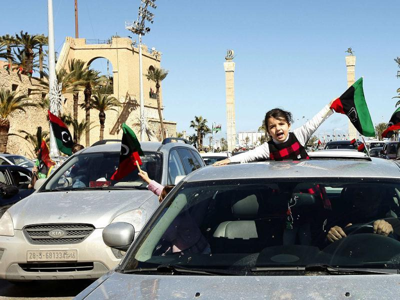 A girl waves a Libyan independence flag as families parade in their cars through the streets of Tripoli to mark the first anniversary of revolutionary uprising against Muammar Gaddafi. Reuters/Ismail Zitouny