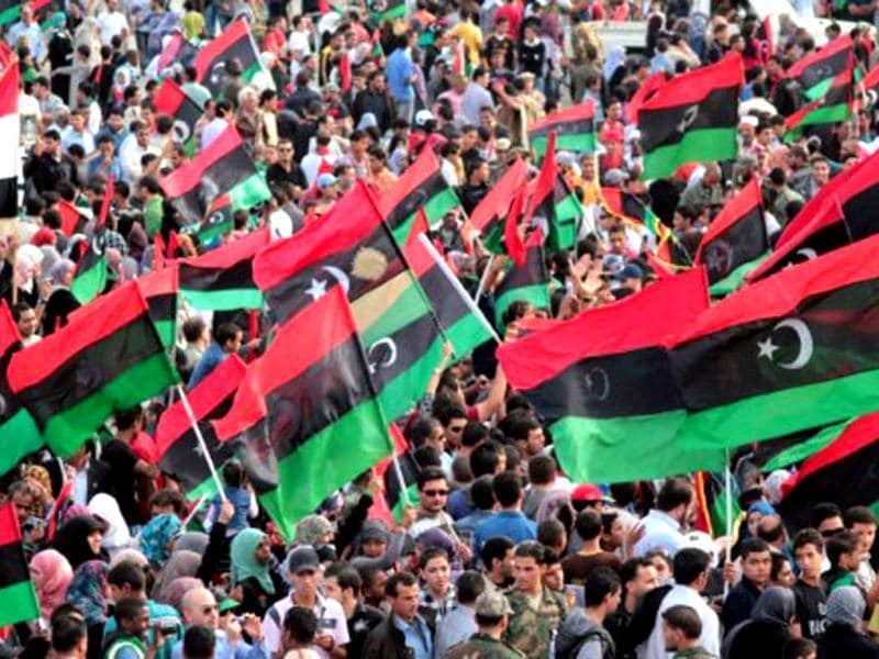 Libyans wave their new national flag as they celebrate following the official liberation of the country in the eastern city of Benghazi on October 23, 2011 three days after ousted despot Muammar Gaddafi was captured and killed. AFP/Abdullah Doma, File