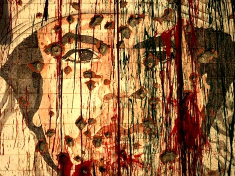 A defaced portrait of fugitive Libyan leader Muammar Gaddafi is pictured in Tripoli. Libya marks the first anniversary of revolutionary uprising against Muammar Gaddafi. AFP/Patrick Baz, File