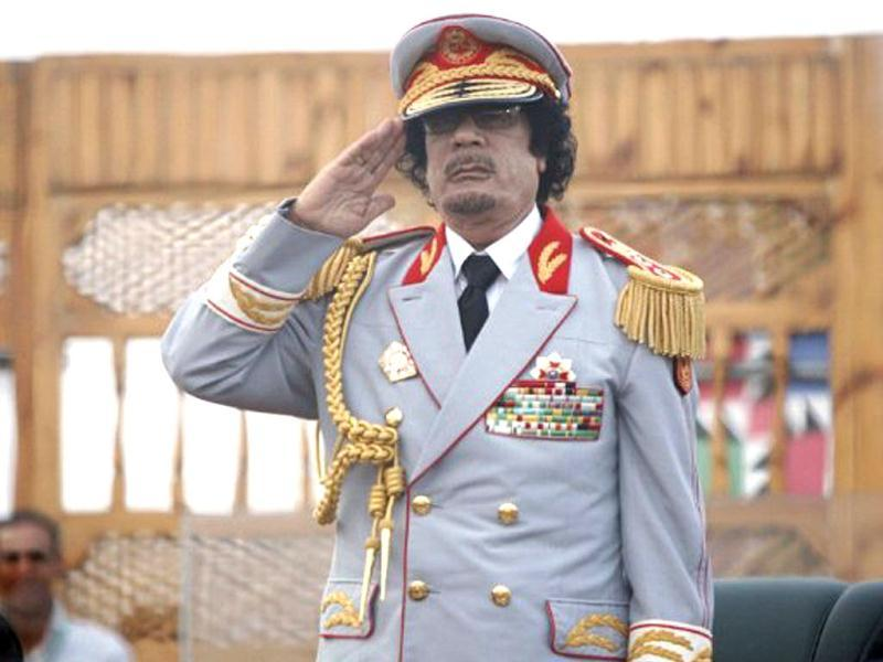 Libyan leader Muammar Gaddafi salutes during the 40th anniversary of the evacuation and expulsion of US forces and bases on Libyan soil. AFP/Mahmud Turkia, File
