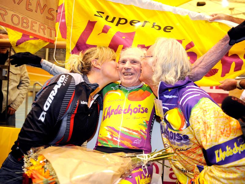 French cycling enthusiast and centenarian Robert Marchand (C) is kissed after setting a new record in the Master 100 years category on the track of the International Union Cycling in Aigle. AFP Photo/Sebastien Feval