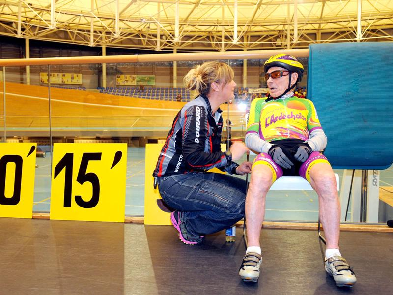 French cycling enthusiast and centenarian Robert Marchand (R) speaks with his coach Magali Humbert after setting a new record in the Master 100 years category on the track of the International Union Cycling in Aigle. AFP Photo/Sebastien Feval
