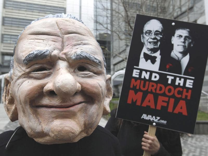 A protester wearing a mask depicting Rupert Murdoch, stages a protest against him, outside the headquarters of News International in London. AP/Lefteris Pitarakis