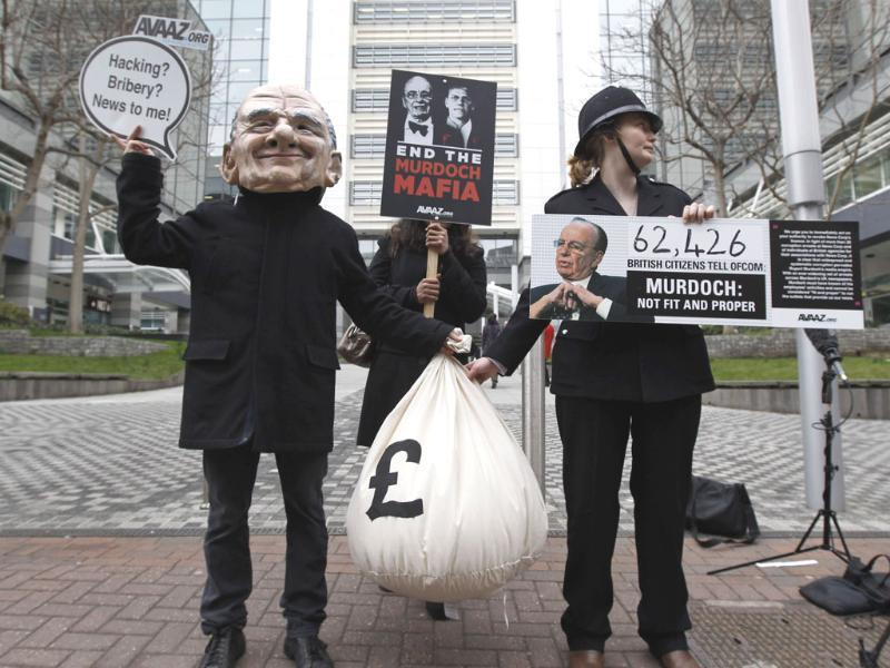 Protesters holding placards and one wearing a mask depicting Rupert Murdoch, left, and one wearing a police uniform, right, stage a rally against him, outside the headquarters of News International in London. AP/Lefteris Pitarakis