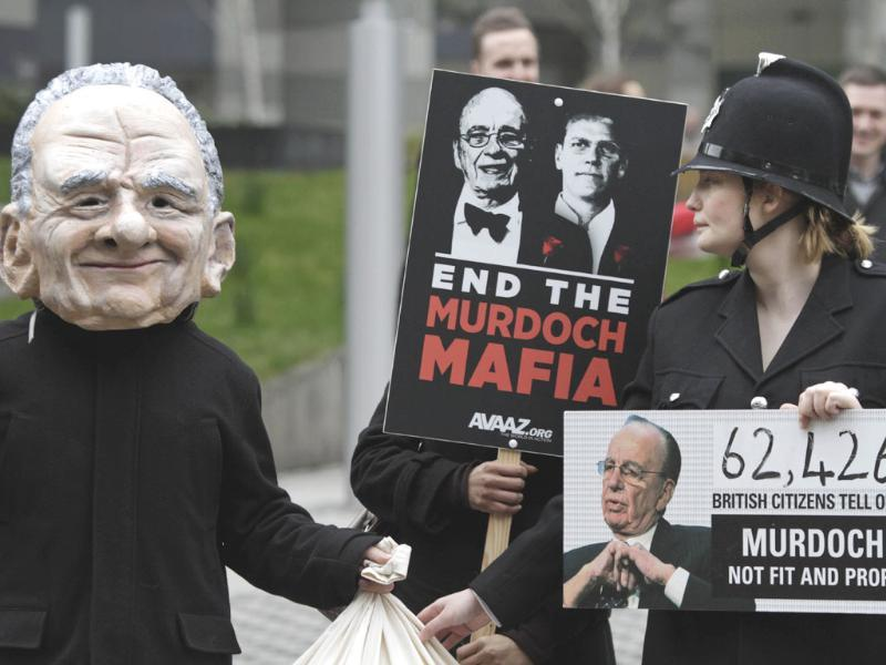 Protesters holding placards and a protester, left, wearing a mask depicting Rupert Murdoch, left, and one wearing a police uniform stage a demonstration against him, outside the headquarters of News International in London. AP/Lefteris Pitarakis