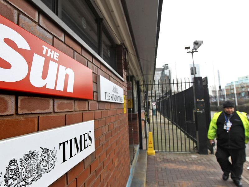 A security guard walks past signs of Rupert Murdoch's News International's titles, outside their headquarters in London. AP/Lefteris Pitarakis