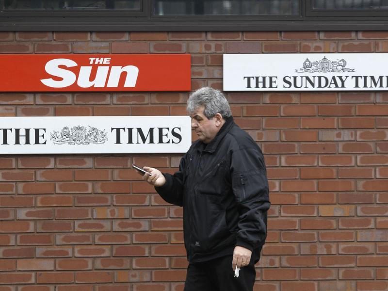 A man walks past signs of Rupert Murdoch's News International's titles, outside their headquarters in London. AP/Lefteris Pitarakis