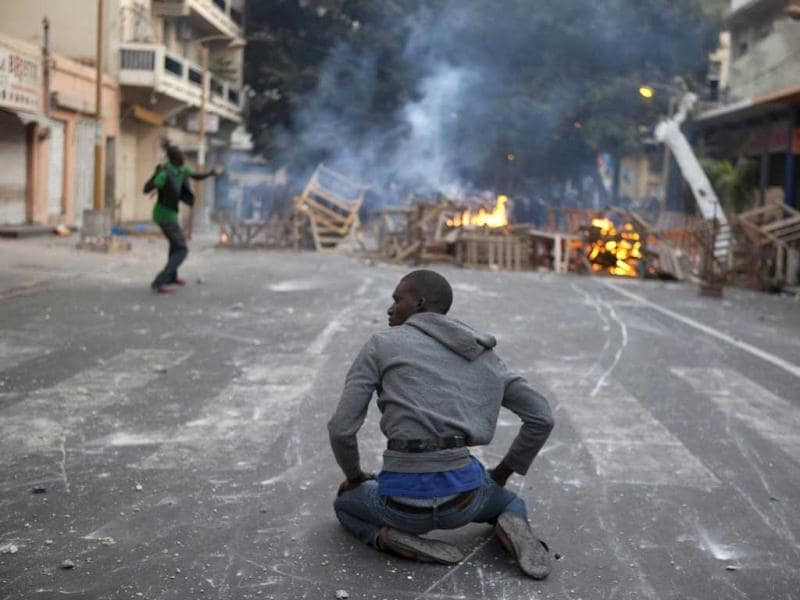 An anti-government protester sits on the ground while another (L) throws rocks at police in Dakar. Reuters/Joe Penney