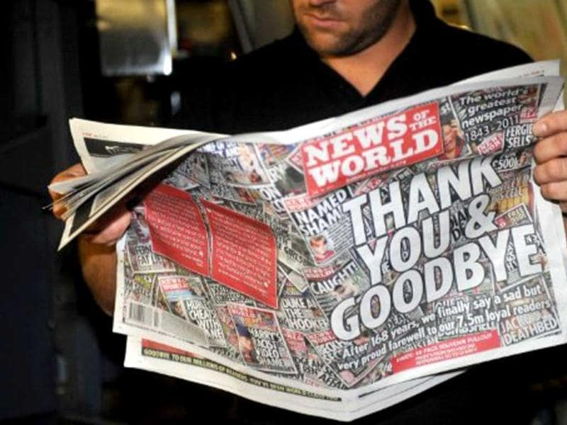 Printer James Bradley reads the final edition of the British tabloid newspaper News of the World as it rolls off the press at the News International print works in Waltham Cross, Hertfordshire. AFP Photo