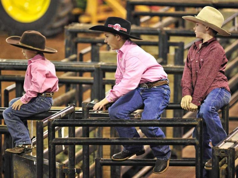 Jaggar White (L-R), 6, and his brother Kolton, 8 of Kenansville, Florida and Wes Kempfer, 8, of Melbourne, Florida watch the ground crew set up the 128th Silver Spurs Rodeo held at Osceola Heritage Park in Kissimmee, Florida. This is the biggest rodeo east of the Mississippi River, and is so important to the community that all public schools in the county close for the day. REUTERS/Octavian Cantilli