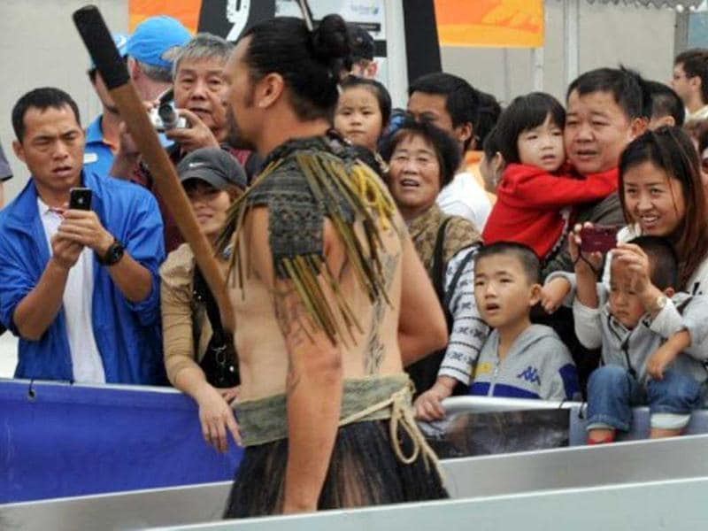 Chinese yachting fans react as a Maori warrior walks to the Camper/Team New Zealand boat before the In-Port-Race which was eventually won by Spain's Team Telefonica on the eve of the Volvo Ocean Race departure from Sanya, Hainan Island. AFP Photo/Mark Ralston