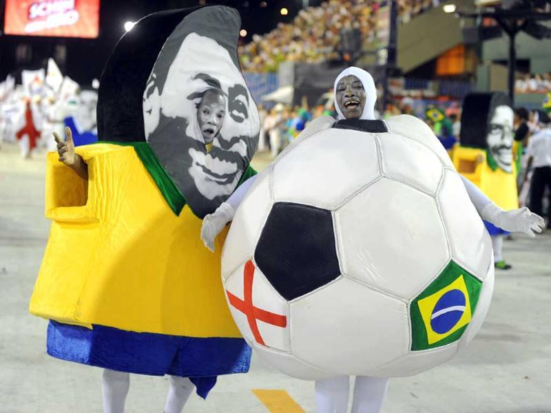A reveller of Uniao da Ilha samba school disguised as Brazilian football star Pele performs with a reveller disguised as a ball during the second night of carnival parade at the Sambadrome in Rio de Janeiro. AFP/Antonio Scorza
