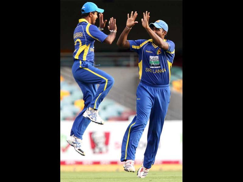 Sri Lanka's Nuwan Kulasekara, left, celebrates with teammate Thisara Perera after the wicket of Virender Sehwag during their One Day International cricket match in Brisbane. AP Photo/Tertius Pickard