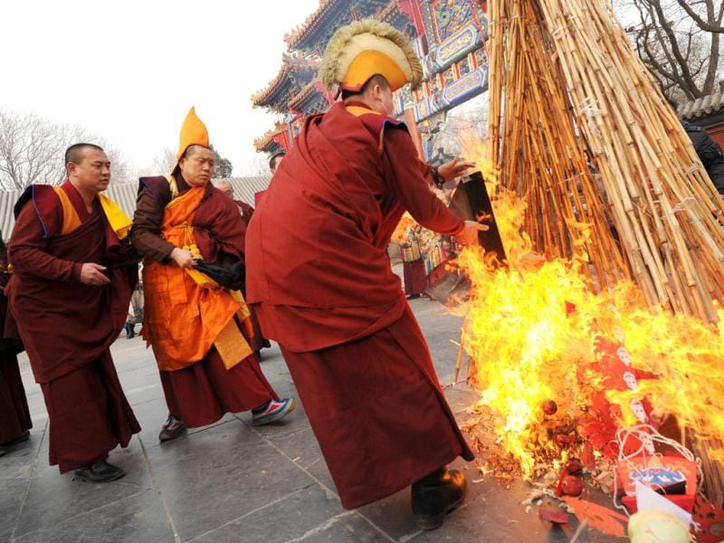 Tibetan monks throw a skull effigy into flames during a Tibetan New Year ceremony at the Yonghe Temple, also known as the Lama Temple in Beijing. AFP Photo/Mark Ralston