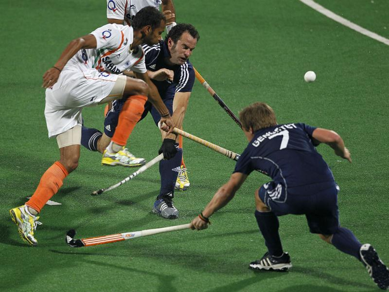 France's Frederic Verrier, center, reacts as Sunil Vitalacharya Sowmarpet crashes against him during their field hockey Olympic qualifier in New Delhi. On the right is France's Hugo Genestet.(AP Photo)