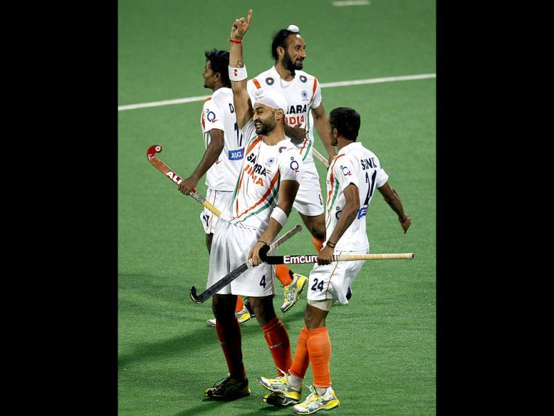Sandeep Singh, center, gestures after scoring India's fifth goal as teammates celebrate around him during their field hockey Olympic qualifier against France in New Delhi. (AP Photo)